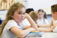 A close up shot of a little girl at school who looks distant and upset.