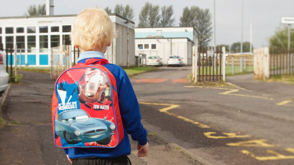 Boy with rucksack at school entrance